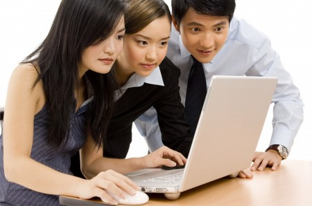 Due donne e un uomo orientali al laptop