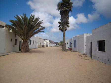 Larga via sabbiosa con palme e case bianche squadrate