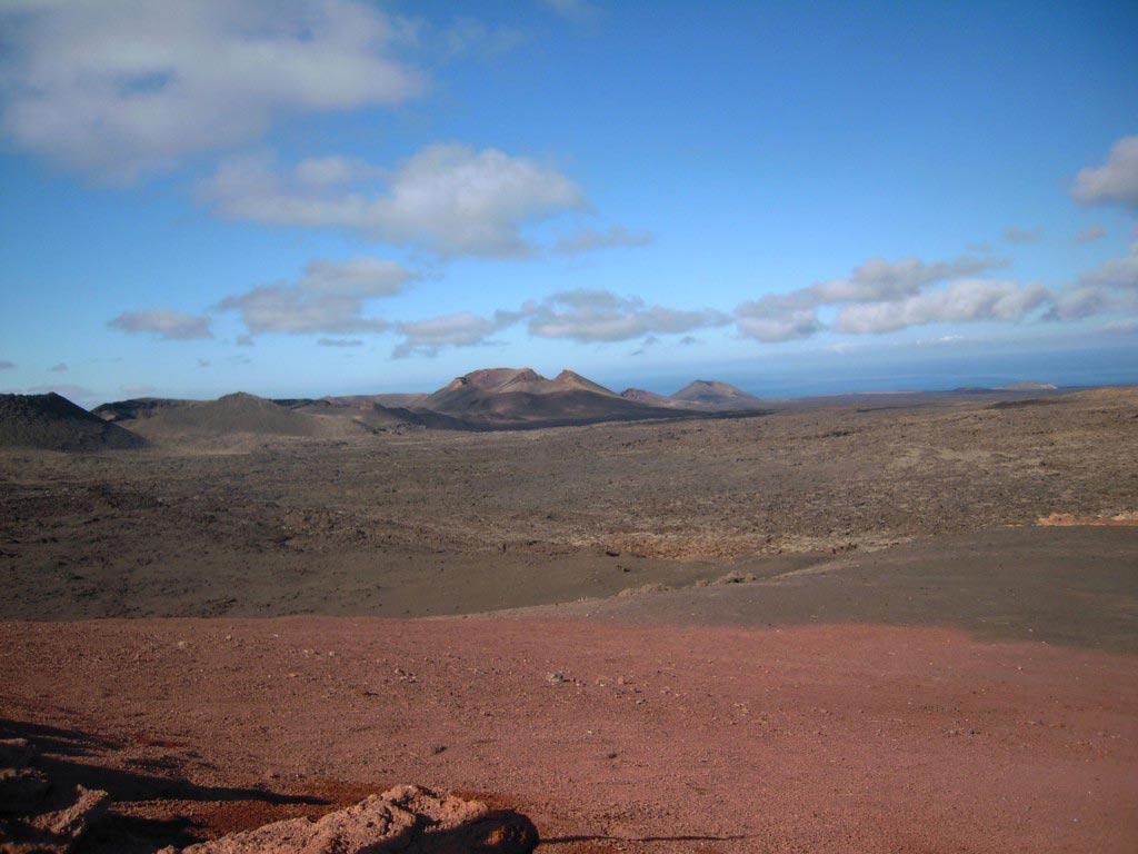 Terra rossa e marrone con vulcano in fondo