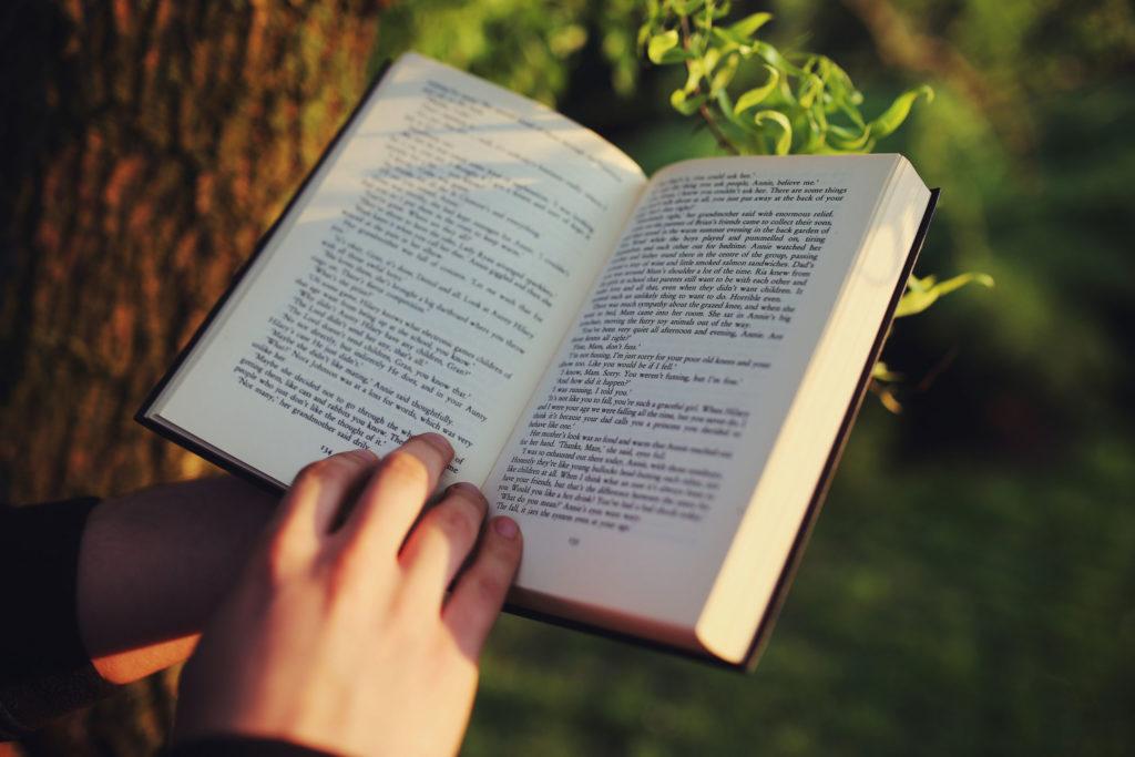 Lettura di un libro in mezzo al verde. Primo piano sul libro e sulle mani