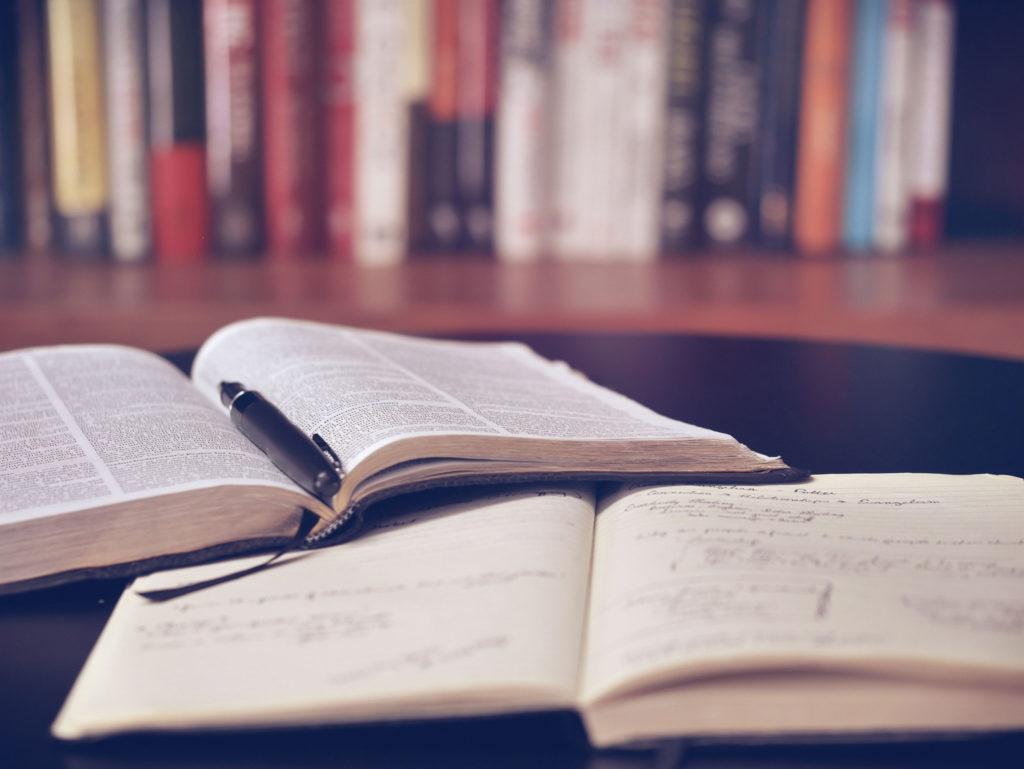 Libri aperti sul tavolo con penna e libreria